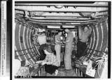 Men and a woman working on plane interior, September 1951