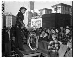 Auctioneer at police bicycle auction, December 10, 1949