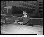 Meter maid Rose Marie Sillence ticketing car, Seattle, November 26, 1957