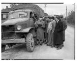 Soldiers and Japanese Americans standing by truck, March 25, 1942