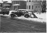 Man pushing a car from a snow-filled parking place, November 20, 1946