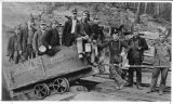 Group of miners and mine car at mine entrance, ca. 1910