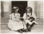 Two girls sitting on porch with cat and doll, 1900