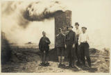 Men standing on a burning slag pile, ca. 1925
