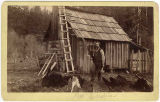 Pat Carrigher standing by cabin, ca. 1889
