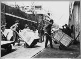 Longshoremen unloading cargo from a freighter by handtruck, 1906