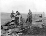 Three men and a rocker in the Nome gold fields, ca. 1905