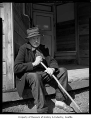 Coal miner Joe Shimmel on steps of abandoned store, Ravensdale, April 14, 1955
