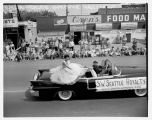 Two princesses sitting on a car during Pancake Festival parade, White Center, August 1956