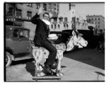 Royal Brougham holding a cake and riding a toy horse, Seattle, November 30, 1936