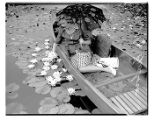 Dorothy Buelow picks water lilies from a canoe, Seattle, September 5, 1942