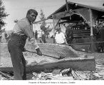Quileute Chief Howeattle demonstrating the building of a dugout canoe, ca. 1930