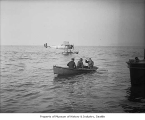 Explorers Richard E. Byrd and George Hubert Wilkins being rowed from floatplane, probably in...
