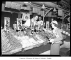 Woman shopping at Dominik Yellam's vegetable stand in Pike Place Market, Seattle, 1939