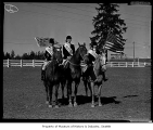 Three women on horseback with American and British flags and suited for a horse jumping show, 1958