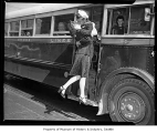 Sailor and a woman kissing goodbye as he boards at the Seattle bus terminal, 1948