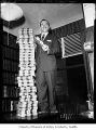 Dan P. Danilov standing on a table beside a stack of Washington Reporters, possibly in Seattle,...