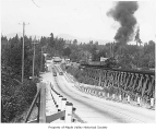 Railroad trestle and train near highway, Maple Valley, ca. 1940