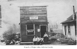 Norman Bains' Barber Shop and Baths exterior showing people outside entrance, Maple Valley, 1913