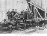 Workers loading a motor from flat car at Continental Coal Company, Ravensdale, 1920