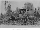 Abe Dubigk with horse and buggy and a locomotive in the background, probably in Maple Valley, n.d.