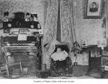 Gibbon residence interior showing baby Chester and an organ, Maple Valley, 1899