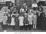 Hobart School first and second grade class standing outside school entrance with Gladys Hughes,...