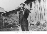 George Sidebotham standing outside and holding a pumpkin, Hobart, ca. 1916