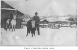 Man with a horse and another with a cow on a ranch in winter, n.d.