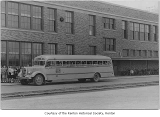 Renton High School exterior showing Renton school bus and students, Renton, n.d.