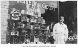 Square Deal Grocery exterior showing James Martin outside a window display, Renton, ca. 1925