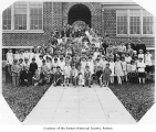 Saint Anthony's Catholic School first grade class with faculty and staff outside school entrance,...