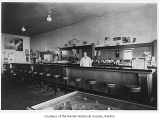 Azzola Tavern interior showing Lino Azzola behind the bar, Renton, 1937
