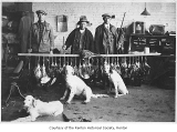 Pheasant hunters and hunting dogs inside an office, probably in Renton, 1927