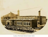 Henry Ford School exterior showing a group portrait of students and teachers from across the...