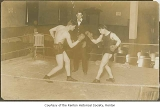 Dan Hogan and Shorty Mossan boxing while referee Tom Swift looks on, possibly in Renton, n.d.