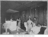 Renton Laundry interior showing workers and piles of laundry, Renton, 1911