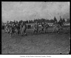 Michael Cooper running with football during a game, Renton, ca. 1908