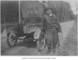 Francis Kane next to a car on a dirt road, possibly in Renton, n.d.