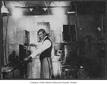Dan Anderson inside the Grand Theatre projection booth with hand crank movie projector, Renton,...