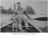 Frank Pritchard Sr. and dog in canoe on Lake Washington, Seattle, ca. 1920