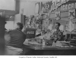 Chuck Roselli behind counter at York Pharmacy, Seattle, ca. 1935