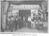 Men in doorway of Rainier Valley Barber Shop and AYP Pool Room, Seattle, 1909