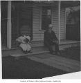 G.S. Dudley and his grandson Hawley with cat on porch of Dudley home, Columbia City, 1905