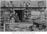 Chuck Roselli behind counter in York Grocery, Seattle, ca. 1935