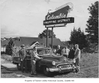 Columbia Merchants officers under Columbia Shopping District sign, Seattle, 1950