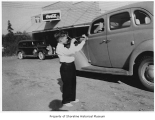 Don Leland playing violin outside Leland's Grocery, Lago Vista, ca. 1938