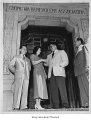 Four people in doorway of Chong Wa Benevolent Association, Seattle, July 1952