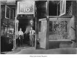 Three men inside doorway of Swift Cafe, Seattle, 1910
