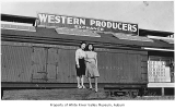 Western Producers Exchange, exterior, with Toshi Ishahara and Mae Iseri Yamada standing near a...